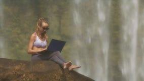 Flickan i violetöverkant arbetar med bärbara datorn på stort vaggar arkivfilmer