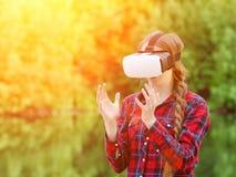Flickan i virtuell verklighetexponeringsglas rymmer henne händer främst av Arkivbild