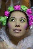 Flickan i vit skyler med rosen, och gräsplan blommar Arkivfoton