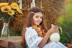 Flickan i vita drinkar för en klänning mjölkar från en tillbringare i sommaren nära höstacken Royaltyfria Bilder