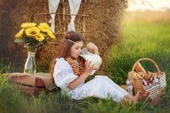 Flickan i vita drinkar för en klänning mjölkar från en tillbringare i sommaren nära höstacken Royaltyfri Fotografi