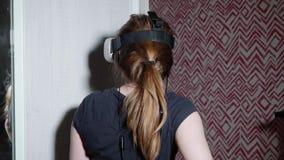 Flickan i VR-exponeringsglas är ställningar och samtal som kommenterar någon saker lager videofilmer