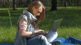 Flickan i yoga poserar med bärbara datorn En tonårs- flicka på naturen skriver på en bärbar dator En tonåring i jeans och armband arkivfilmer