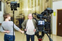 Flickan intervjuar mannen Video skytte i inre Lcd-skärm på camcorderen royaltyfri fotografi