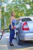Flickan kör bilen på bensinstationen royaltyfri fotografi