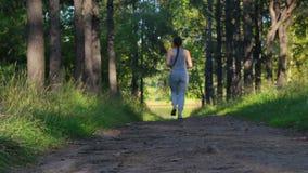 Flickan kör längs en skuggig gränd för skoggräsplan rustande parkkvinnabarn stock video