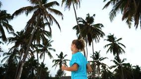 Flickan kör omkring i morgonen i palmträden på gryning lager videofilmer
