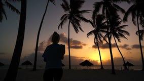 Flickan kör omkring i morgonen i palmträden på gryning stock video