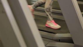 Flickan kör på en trampkvarn i idrottshallen Begrepp för kondition Närbild lager videofilmer