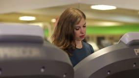 Flickan kör på en trampkvarn i idrottshallen, det reflekteras i speglarna stock video