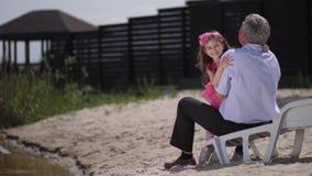 Flickan kör till hennes farfar, kramar hans hals och leenden på kameran 4K l?ngsam mo lager videofilmer