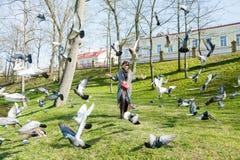 Flickan kör till och med en flock av duvor Royaltyfri Foto