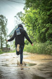 Flickan kör till och med pölar i regnigt sommarväder En landsla Arkivfoto