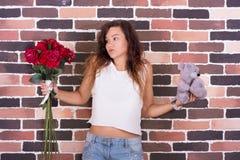 Flickan kan inte avgöra vilken gåva är bättre Arkivfoto