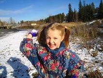 flickan kastar snöboll Arkivbilder