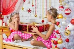 Flickan kikade och såg vad gåvan ska ge henne en annan flicka Fotografering för Bildbyråer