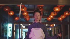 Flickan klädde som danser för en samuraj med ett japanskt svärd lager videofilmer
