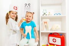Flickan klädde som en tandläkare undersökte hennes vän fotografering för bildbyråer