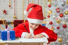 Flickan klädde som Santa Claus som skriver en lista av önskade gåvor för jul Royaltyfri Foto