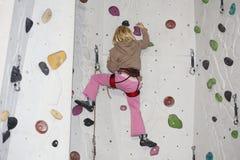 Flickan klättrar på den inomhus väggen arkivbild