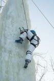 Flickan klättrar uppåt på isklättringkonkurrens Arkivfoto