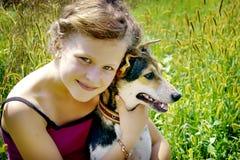 Flickan klamra sig fast intill hennes hund och känner sig lycklig Bra dag av summer_ arkivbilder