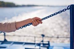 Flickan klamra sig fast intill kedjan på flodbakgrund royaltyfri fotografi