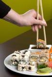 Flickan klibbar tar den smakliga sushi Royaltyfria Foton