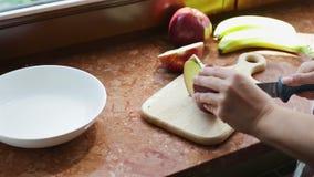 Flickan klipper äpplena för att göra en kaka arkivfilmer