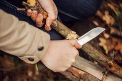Flickan klipper en pinne en kniv Arkivbilder