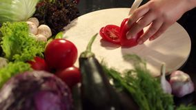 Flickan klipper en tomat med en keramisk kniv CU 4K stock video