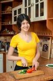 Flickan klipper grönsaker för sallad i köket som lagar mat buller Arkivbild