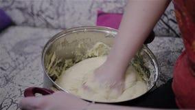 Flickan knådar degen i en stor kruka close upp Laga mat en stor kaka och bröllopstårtor