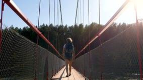 Flickan kommer med en ryggsäck på bron stock video