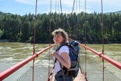 Flickan kommer med en ryggsäck på bron Arkivbilder