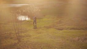 Flickan kommer ner från kullen till hennes pojkvän som står nära sjön Ett älska par spenderar tid tillsammans under arkivfilmer