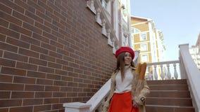 Flickan kommer ner i en röd basker längs trappan med bagetter i hennes händer arkivfilmer