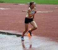 Flickan konkurrerar i den 3.000 räkneverk steeplechasen Arkivfoton