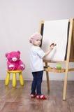 Flickan konstnären drar på stafflibjörn Royaltyfri Fotografi