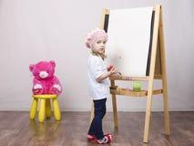 Flickan konstnären drar på stafflibjörn Royaltyfria Bilder