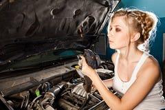 Flickan kontrollerar den olje- nivån i bilen Royaltyfri Fotografi