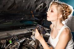 Flickan kontrollerar den olje- nivån i bilen Arkivbilder