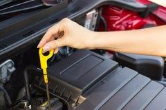 Flickan kontrollerar den olje- nivån i bilen, begreppet av problemet på vägen royaltyfria foton