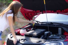Flickan kontrollerar oljanivån i bilen royaltyfri fotografi