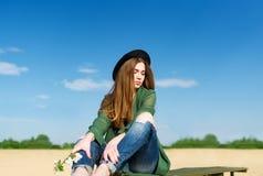 Flickan kopplar av på den sandiga stranden på floden Royaltyfri Bild