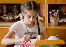 Flickan kopplas in i favorit- affär, drar målarfärger royaltyfri foto