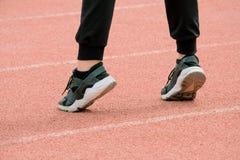 Flickan kopplas in i kondition Kvinnlign lägger benen på ryggen i svarta gymnastikskor, och flåsanden står på sockor på bakgrunde arkivfoto