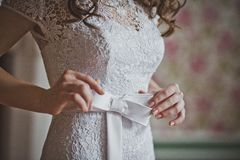 Flickan korrigerar en pilbåge på en klänning 2648 Arkivbilder