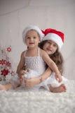 Flickan kramar hennes lilla syster, båda bärande röda jullock och arkivfoto