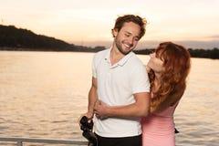 Flickan kramar hennes par på yachten, under solnedgång royaltyfri fotografi